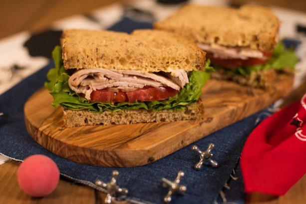 Sanduíche de Peito de Peru defumado, tomate, alface e pão integral, com maionese dijon. Woodys Lunch Box Toy Story Land